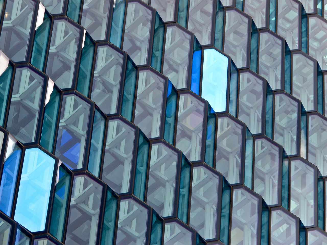 The structure consists of a steel framework clad with geometric shaped glass panels of different colours. The building was originally part of a redevelopment of the Austurhöfn area dubbed World Trade Center Reykjavík, which was partially abandoned when the financial crisis took hold. The development was intended to include a 400-room hotel, luxury apartments, retail units, restaurants, a car park and the new headquarters of Icelandic bank Landsbanki.  Today, it is just a concert hall with restaurants on the main level.