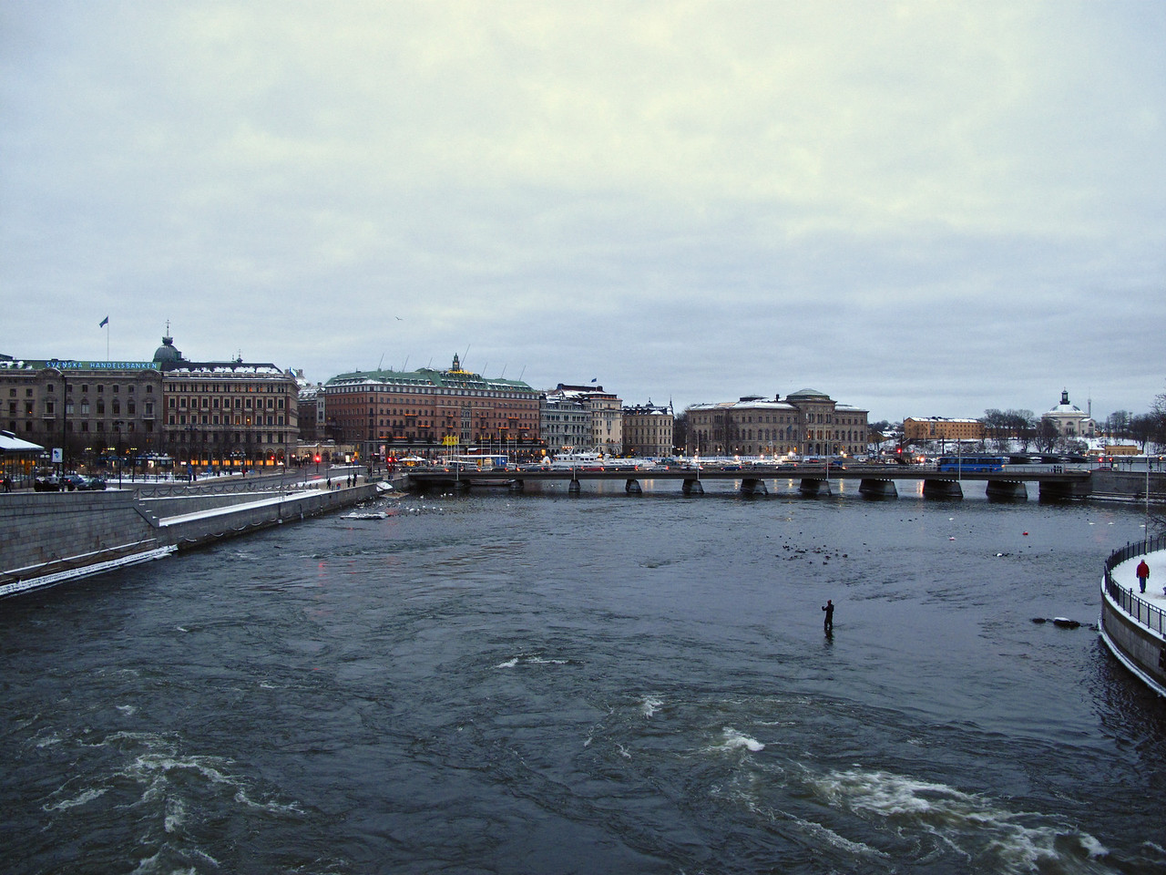 The city of Stockholm is spread over 14 different islands.  There are many bridges and water crossings throughout the city.  Here, a fly fisherman takes a chance in very icy waters.