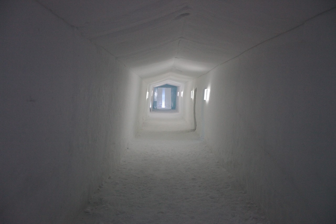 One of the corridors off of the Ice Hall with rooms on each side.  There are no doors on the rooms, just small wool privacy curtain.  In each room the only light is provided by minimal LED light.  There's also a small hole in each ceiling that ventilates to the outside.