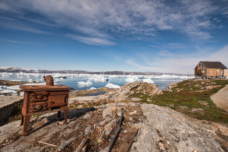 An old rusty stove on the rocks outside Tinit overlooking Sermilik Fjord