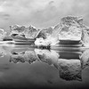 Black and white image of an iceberg and its mirror image
