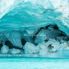 A turquoise green ice cave in an iceberg, Sermilik Fjord