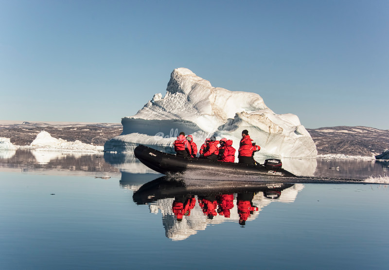 Zodiac passing in front of a small iceberg, Sermilik Fjord