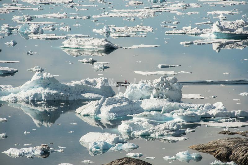 A lone boatman travels amidst the icebergs of Sermilik Fjord