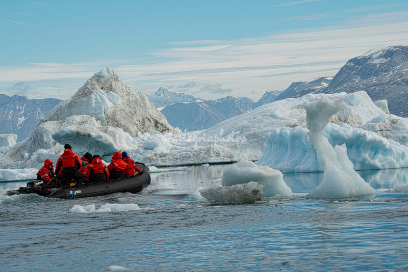 A Zodiac inflatable boat is used to explore the Sermilik Fjord