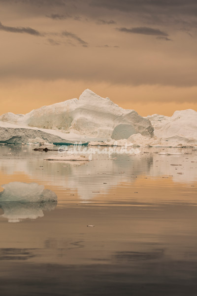 Iceberg at sunset on a cloudy day