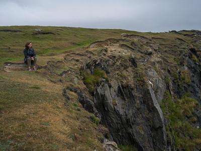 Woman sitting on cliff, Achill Island, County Mayo, Ireland