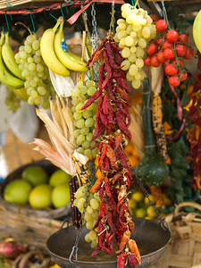 Dry red chili peppers hanging with fruit at a market stall, Positano, Amalfi Coast, Salerno, Campania, Italy