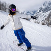 Woman snowboarding on slopes, Alpine Resort, Aosta Valley, Courmayeur, Northern Italy, Italy
