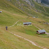 A hiker walks across the meadow in the mountains above Ortisei, Val Gardena, Dolomites, Italy