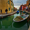 A fishing net lies ready on the front of a boat in the Burano canal, Venice