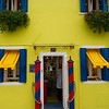 Blue and red striped poles decorate a yellow structure in Burano, Venice