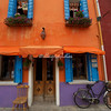 A multicolored building with bicycle and chair, Burano, Venice
