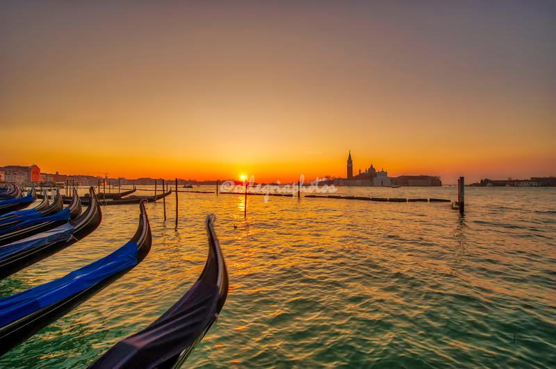 View along line of Gondolas and San Giorgio Maggiore at sunrise