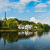 View of Nidaros Cathedral and the colored wooden houses, from across the Nidelva River, Trondheim, Norway.