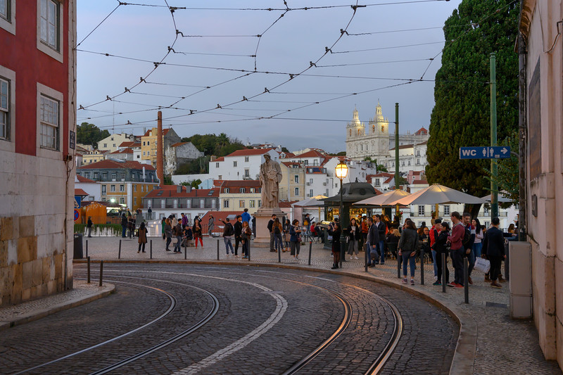 People on street with Monastery of Sao Vicent de Fora in the background, Sao Miguel, Lisbon, Portugal