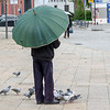 Person standing with umbrella near pigeons, Santa Marinha, Porto, Portugal