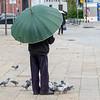 Person standing with umbrella near pigeons, Santa Marinha, Porto, Portugal