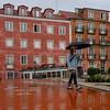 Woman walking with umbrella in rain, Miradouro De Santa Luzia, Sano Miguel, Lisbon, Lisboa Region, Portugal