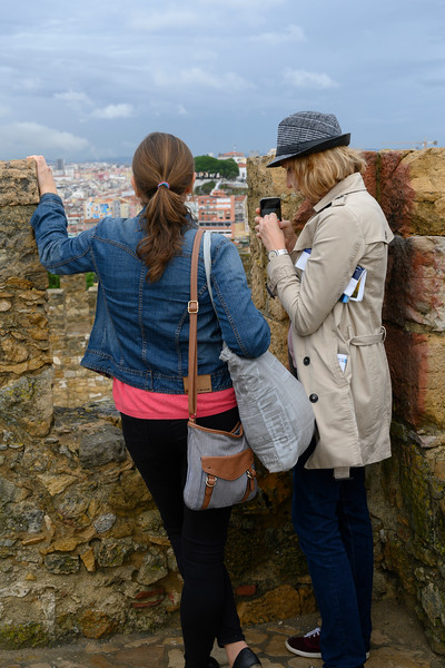 Tourists looking at city from old walls of St. George's Castle, Castelo, Lisbon, Portugal