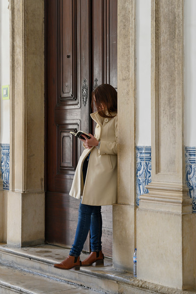 Woman standing at doorway reading a book, Coimbra, Coimbra District, Portugal