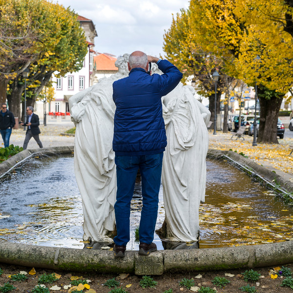 Elderly man taking picture of statues in park, Viseu District, Northern Portugal, Portugal