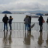 People at waterfront in rain, Alfama, Sao Miguel, Lisbon, Portugal