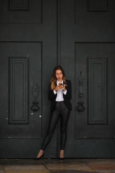 Businesswoman using mobile phone and smoking cigarette, Sao Nicolau, Lisbon, Portugal