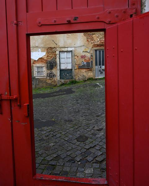 Cobblestone road seen from open door, Alfama, Sao Miguel, Lisbon, Portugal