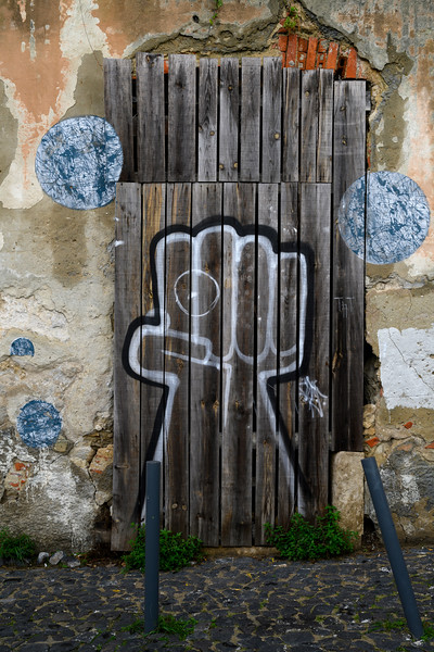 Graffiti on the door of damaged house in Santiago, Lisbon, Portugal