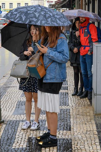 People on sidewalk during rain, Sao Nicolau, Lisbon, Portugal