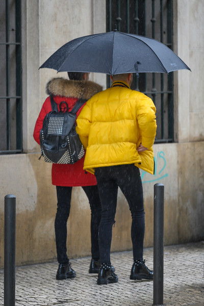 Two men walking under an umbrella on sidewalk, Madalena, Lisbon, Portugal