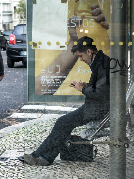 Man sitting at bus stop, Lisbon, Portugal