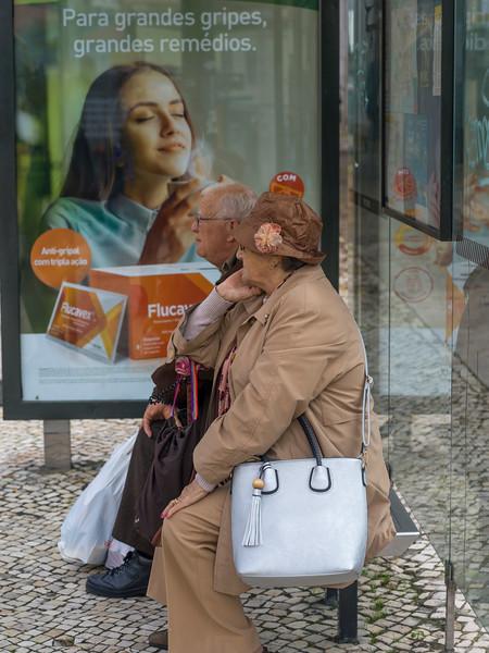 Elderly couple sitting at bus stop, Lisbon, Portugal