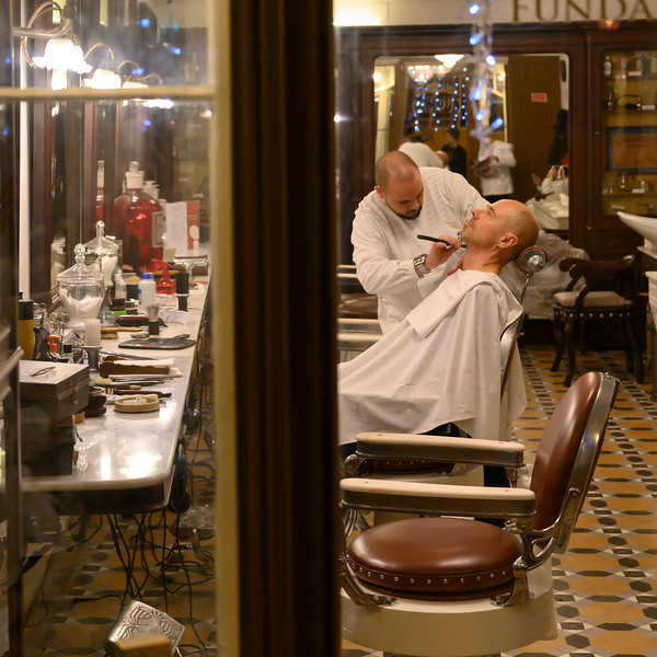 Barber shaving customer in barber shop, Martires, Lisbon, Portugal