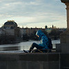 Man sitting on Charles Bridge, Prague, Czech Republic