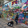 Street performer in front of graffiti covered wall, John Lennon Wall, Prague, Czech Republic