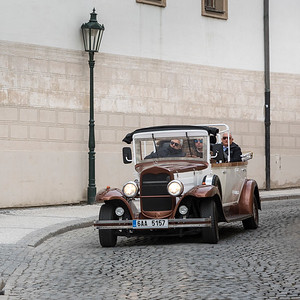 Man driving vintage car on street, Prague, Czech Republic