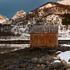 Log cabin at coast with sunlight falling on mountain peak, Lofoten, Nordland, Norway