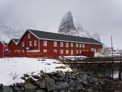 Fishermen houses with snowcapped mountain in the background, Lofoten, Nordland, Norway