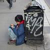 Boy listening to headphones on sidewalk, Stockholm, Sweden
