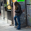 Woman standing on sidewalk using mobile phone, Stockholm, Sweden