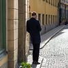 Rear view of man standing on sidewalk, Gamla Stan, Stockholm, Sweden