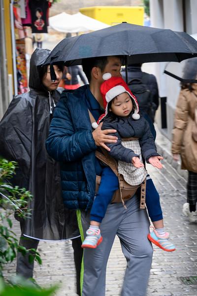 People walking on street during rain, Seville, Seville Province, Spain