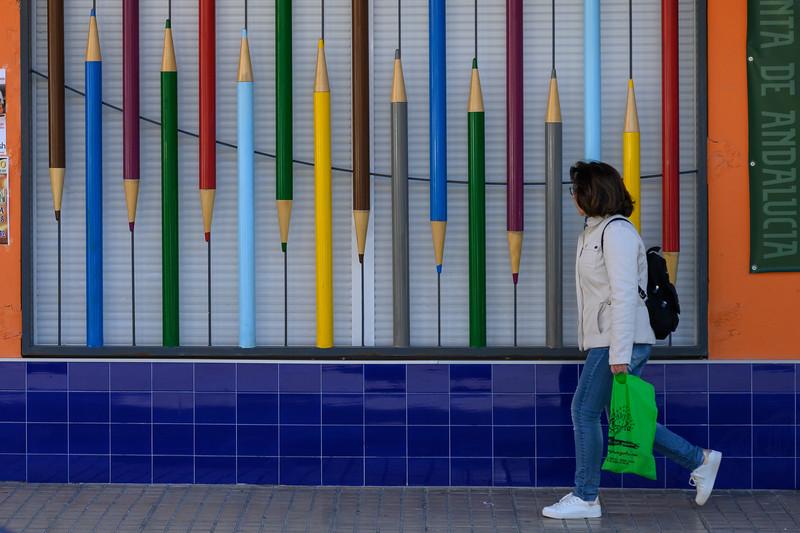 Woman walking by store window display of colored pencils, Ubeda, Jaen Province, Spain