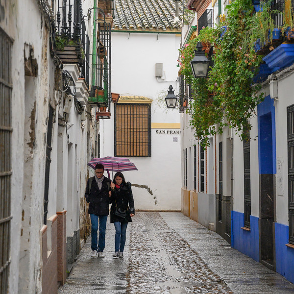 Couple walking along the old town alley in rain, Distrito Centro, C�rdoba, C�rdoba Province, Spain