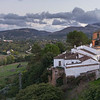 Old town houses and church around mountain in the village of Ronda, Malaga Province, Spain