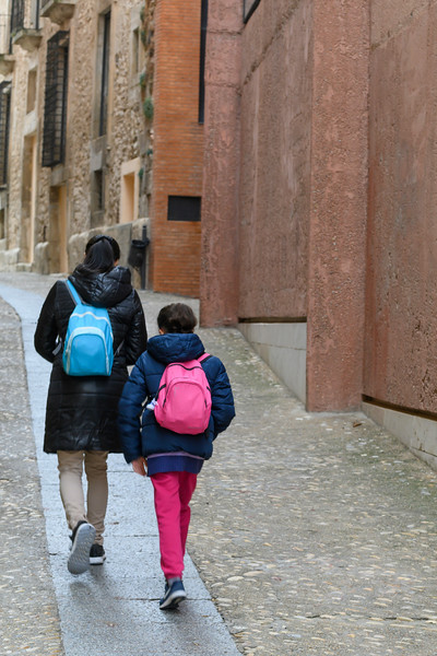 Women and girl walking down the alley of the old historic town in Cuenca, Spain