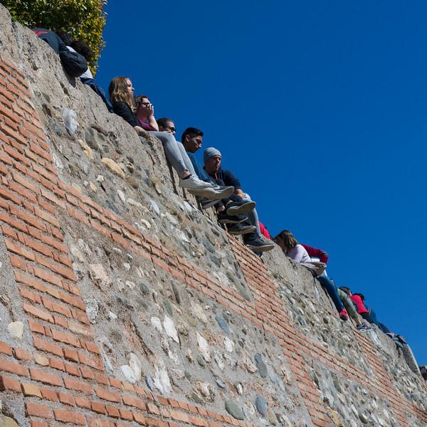 People sitting on edge of a wall, Granada, Granada Province, Spain