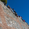 People sitting on edge of a wall, Granada, Granada Province, Spain